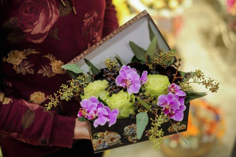 Slut upp för orkidéblomma för nejlika rosa bukett i ask arkivbilder