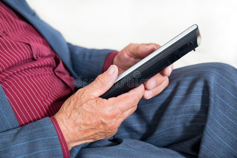 Slut upp fotoet av en hållande fjärrkontroll för gamal manhand arkivbilder