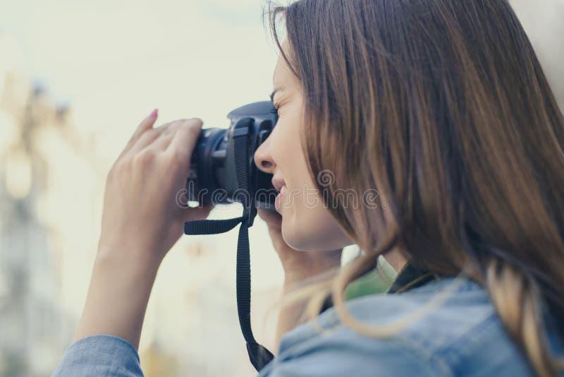 Slut upp fotoet av kvinnan som tar bilden på hennes digicam för att ha lyckliga minnen av en gammal stad, fritid f för skönhetmod royaltyfri foto