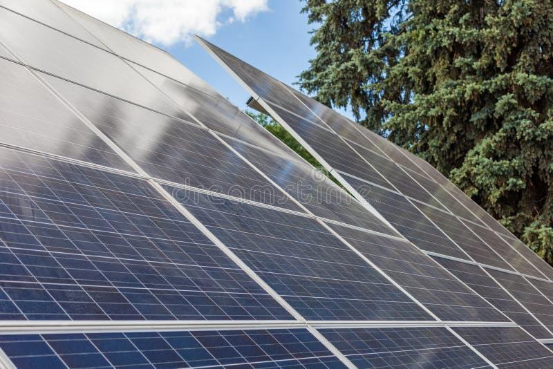 Slut upp fotoet för sidosikt av alternativ solenergi eller ny solenergiutrustning mot blå lugna himmel med det gröna trädet på royaltyfria bilder