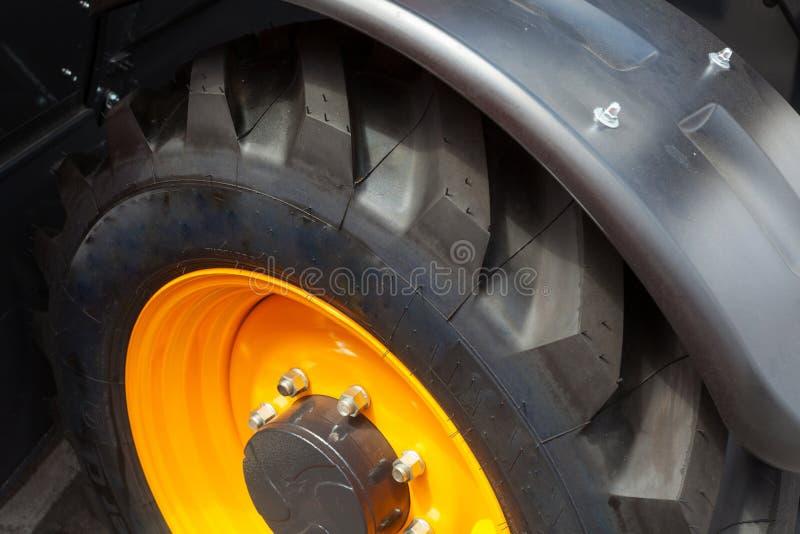 Slut upp fotoet för sidosikt av det enorma gummihjulhjulet för fragment av konstruktion eller åkerbruk automatisk utrustning arkivfoto