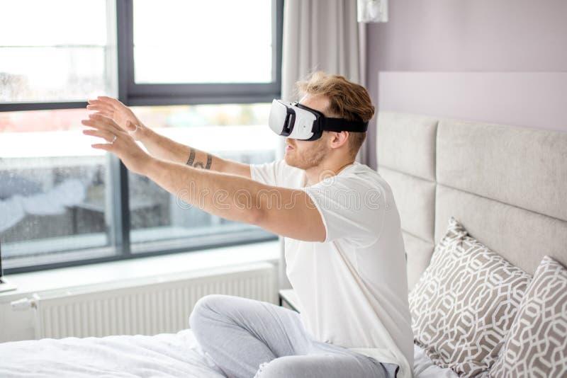 Slut upp fotoet för sidosikt den aktiva angenäma mannen trycker på med virtuell verklighet royaltyfria bilder