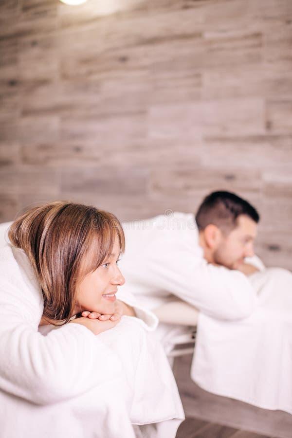 Slut upp fotoet för sidosikt ursnygg ung man och kvinna som ligger på massagesängarna royaltyfri bild