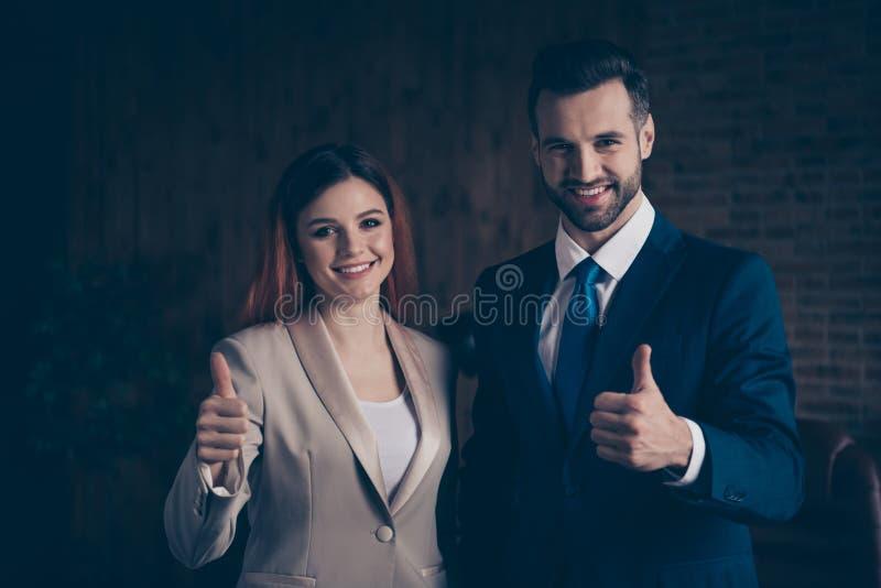 Slut upp fotoet henne hennes affärsdam honom honom hans för prestationfolk för grabb tummar för show för glade par självsäkra bäs fotografering för bildbyråer
