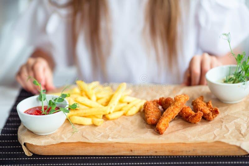 Slut upp frasiga potatissmåfiskar på den vita plattan med doppa sås som två tjänas som på den lantliga trätabellen royaltyfri fotografi