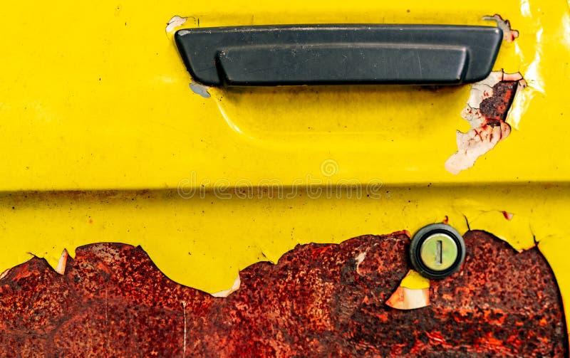 Slut upp gammal bildörr med rostigt Övergiven rostig gul bil med det svarta handtaget Bilfärgläggning skalar Gammal och rostad bi royaltyfria bilder