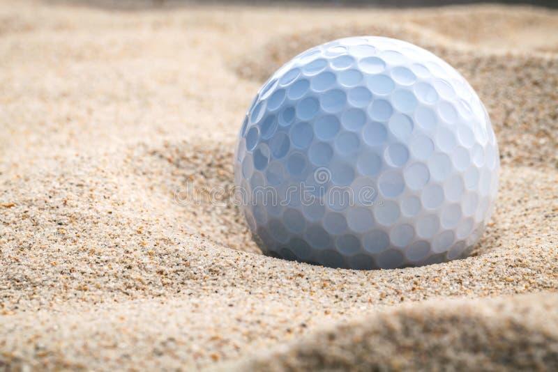 Slut upp golfboll i grunt djup för sandbunker av fältet En gol arkivfoton