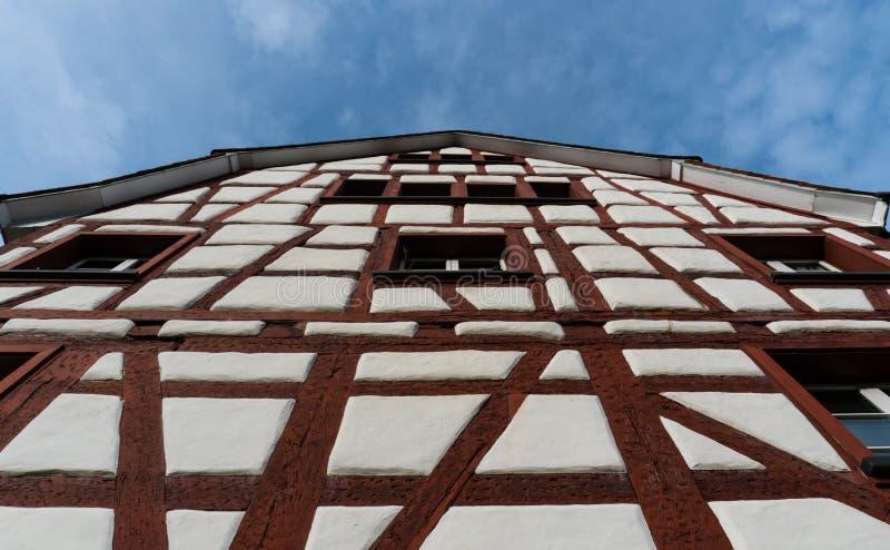 Slut upp grodaperspektivsikt av ett korsvirkes- bråckbandhus med vita väggar och röda trästrålar under en blå himmel arkivfoton
