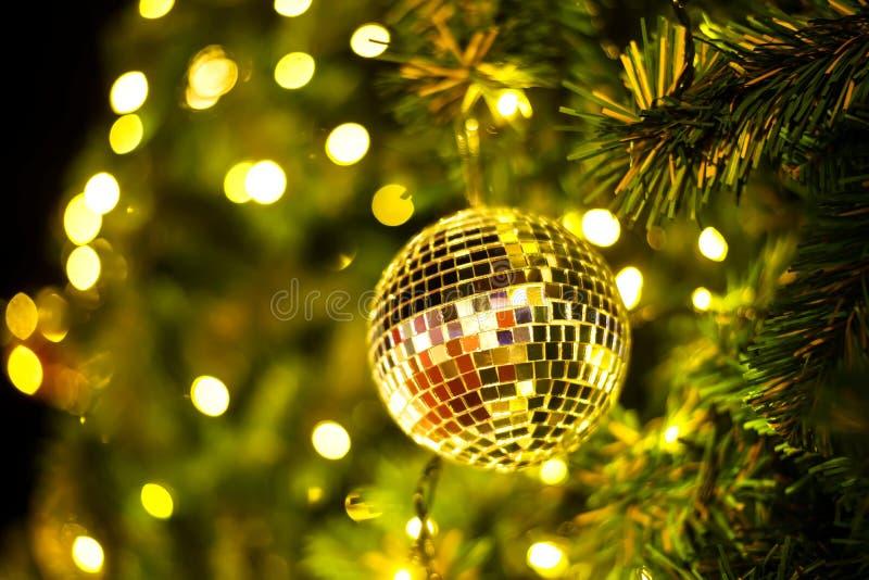 Slut upp guld- bollar av julgrangarneringar på abstrakt ljus guld- bokehbakgrund royaltyfri foto