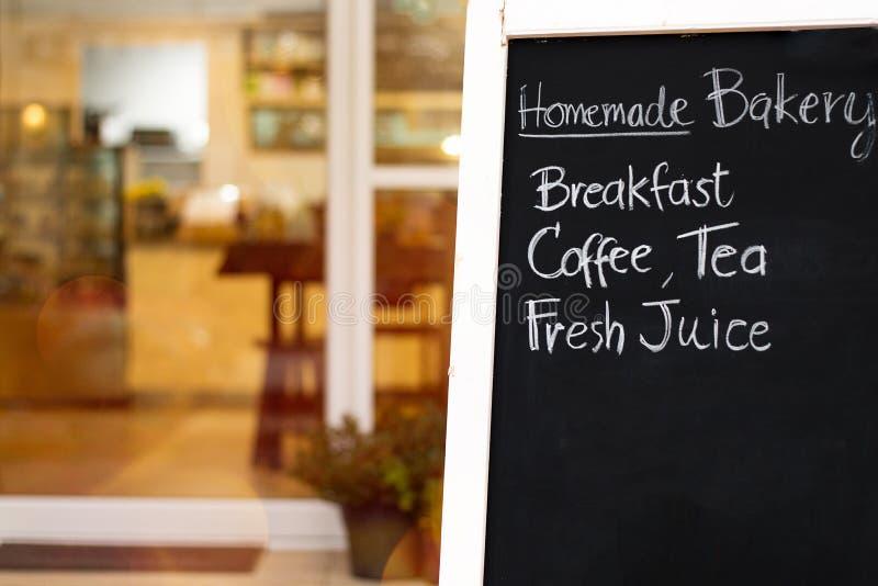 Slut upp härlig handhandstilmeny på svart tavla Svart kritabräde framme av en coffee shopingång Suddiga bageri- och kafélodisar royaltyfria foton