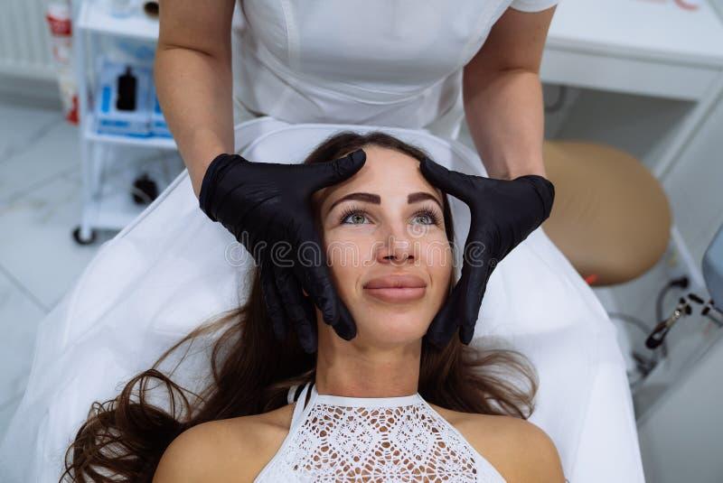 Slut upp härliga kvinnliga händer för framsida- och cosmetologist` s Botox pitt, injektion för hyaluronic syra Föryngring och royaltyfri fotografi