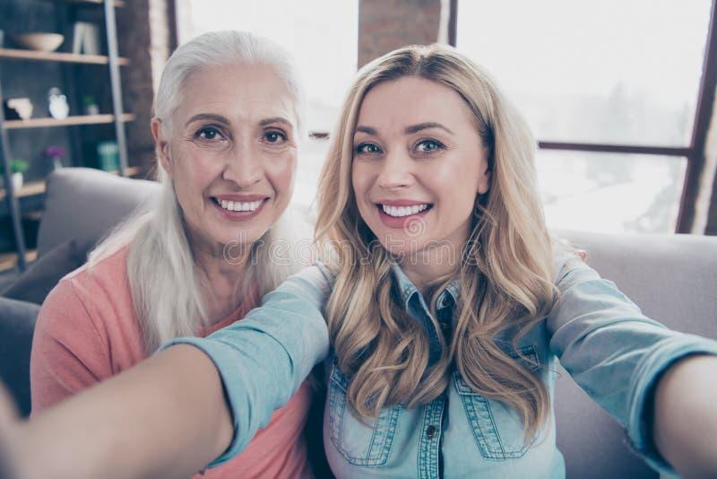 Slut upp härligt foto två henne hennes för farmorsondotter för damer roliga skraj moderna skratt för skratt för mamma för mamma f royaltyfri foto