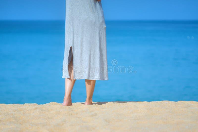 Slut upp h?rlig ung kvinnlig fot barfota som g?r p? sandstranden med havs- och himmelbakgrund Morgondet fria ?var i en su royaltyfri foto
