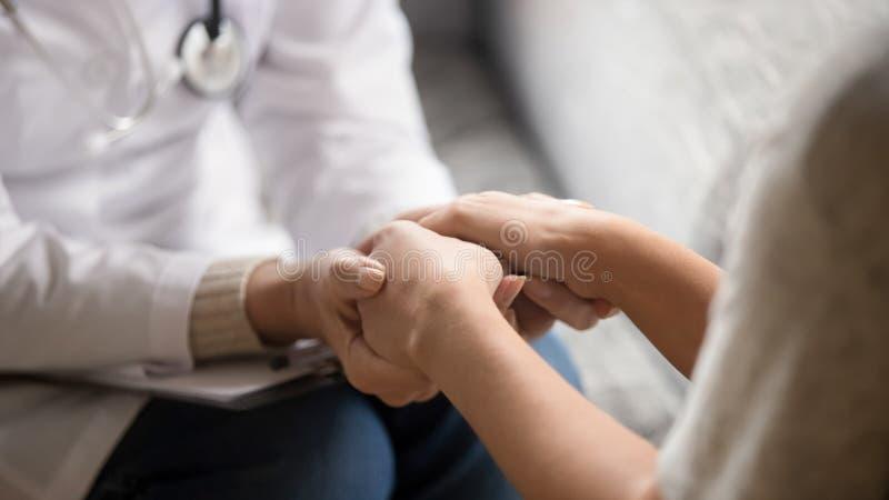 Slut upp horisontalbilddoktorn som rymmer händer av den kvinnliga patienten arkivbilder