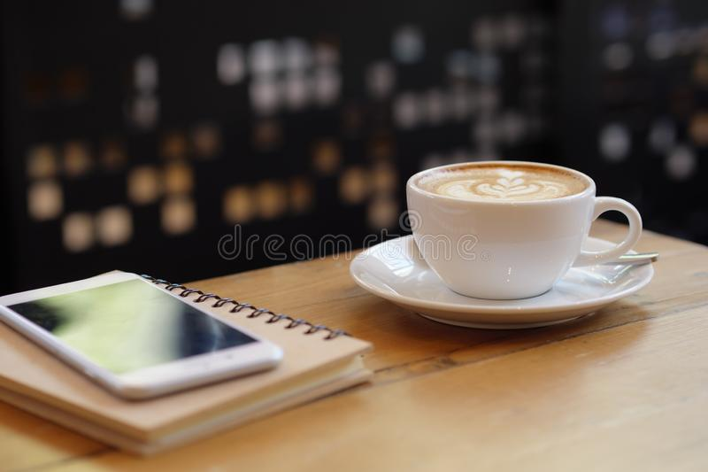 Slut upp koppen för vitt kaffe med lattekonst på trätabellen med smartphonen på coffee shop arkivbild