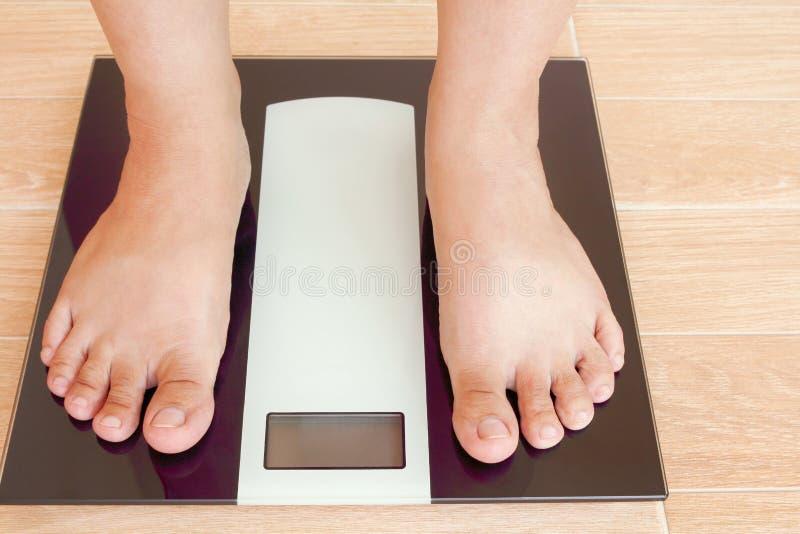 Slut upp kvinnlig fot som står på viktskala med kopieringsutrymme arkivfoton