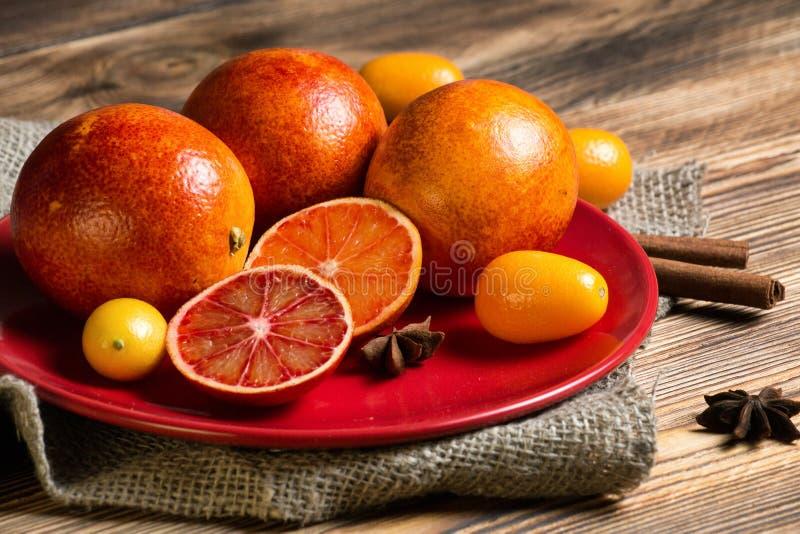 Slut upp läckra röda apelsiner och kumquaten i plattor på träbakgrund arkivbilder