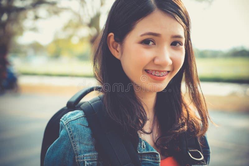 Slut upp leende för framsida för ung asiatisk kvinna för handelsresandefotvandrare lyckligt le med gummi i natur gummin som går t royaltyfri bild