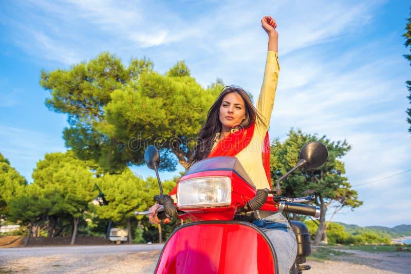 Slut upp livsstilbild av den unga trendiga kvinnan i tillfälligt dräktsammanträde på sparkcykeln på gatan fotografering för bildbyråer