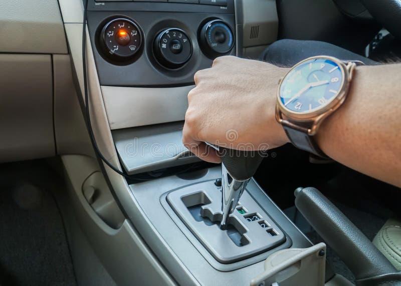 Slut upp man med klockahållen bilkugghjulet, medan köra bilen royaltyfria bilder