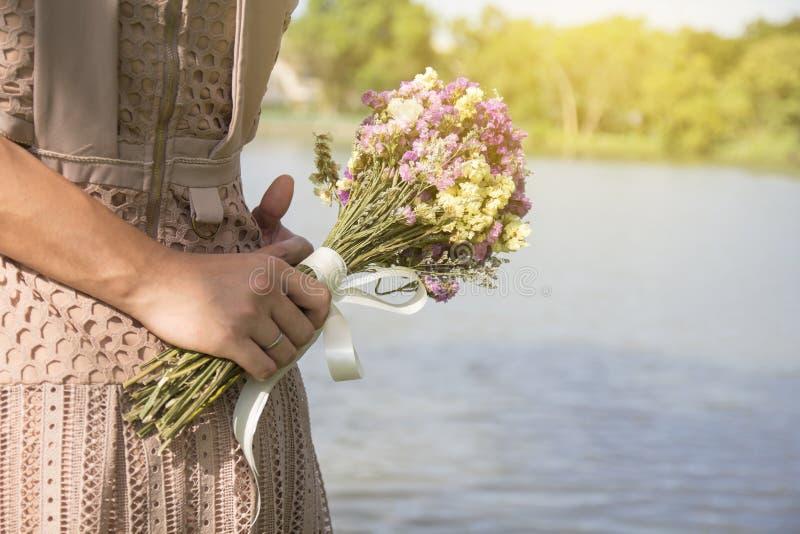 Slut upp manhänder som rymmer blommor och kramar kvinnan fotografering för bildbyråer