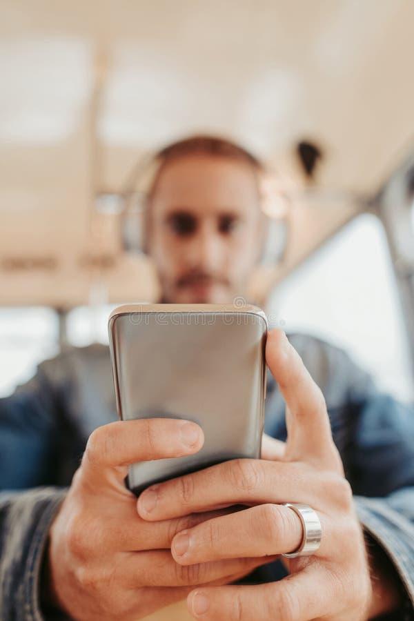 Slut upp manlig lyssnande musik via smartphonen arkivfoton