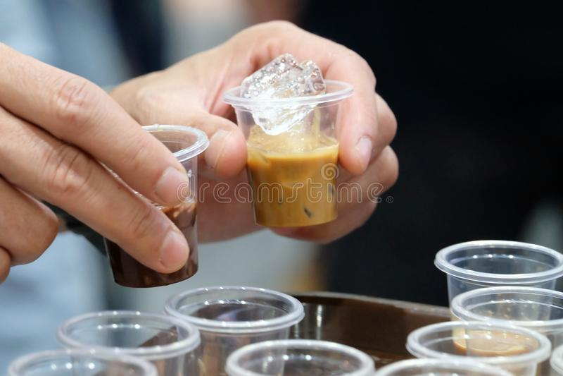 Slut upp manliga händer som rymmer två lilla exponeringsglas av med is lattekaffe och choklad med suddigt många exponeringsglas royaltyfri bild