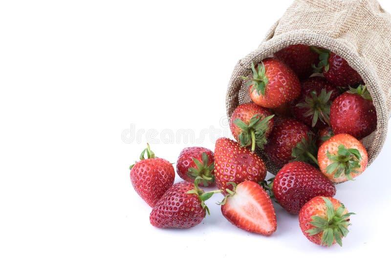 Slut upp nya jordgubbefrukter med skivad halva i säckvävsäcken som isoleras på vit bakgrund frukt och sunt begrepp arkivbilder