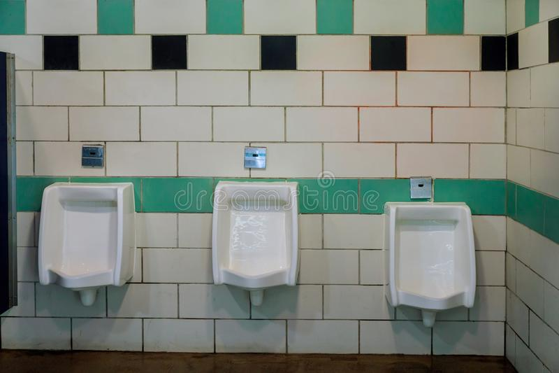 Slut upp offentlig toalett för vita pissoarmän i keramiska pissoar i toalettrum royaltyfri foto