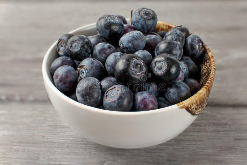 Slut upp på den lilla vita porslinbunken mycket av blåbär royaltyfria foton