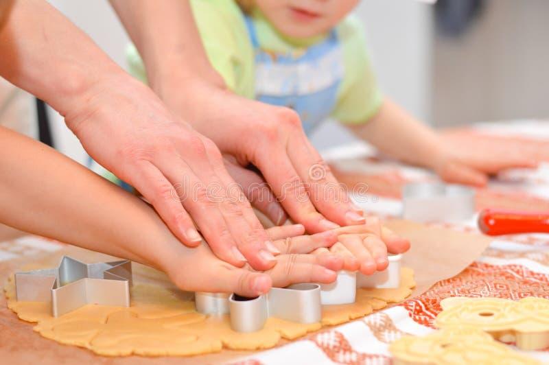 Slut upp på händer som gör pepparkakakakorna med moderhjälp arkivfoto