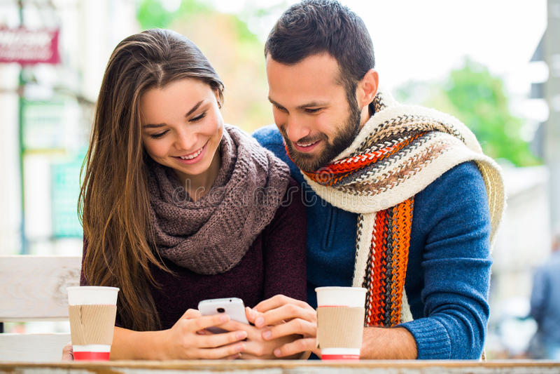 Slut upp - par i hösten parkerar att ta selfie med mobiltelefonen Le par som tar selfie med den smarta telefonen i stadsPA arkivbild