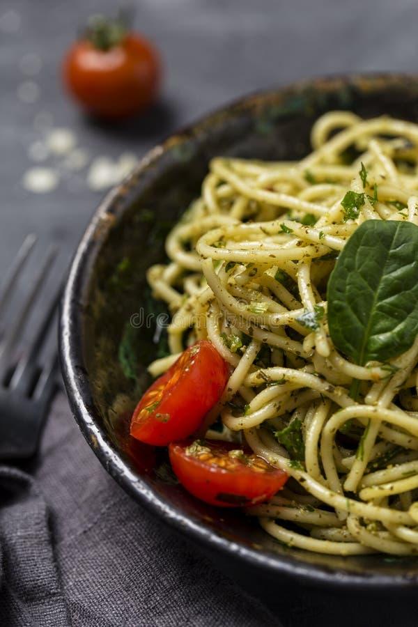 Slut upp pasta med pesto i bunke med körsbärsröda tomater på svart bakgrund royaltyfri bild
