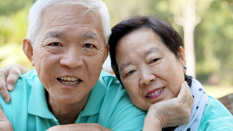 Slut upp potrait av att le asiatiska höga par på ljust - gräsplan arkivbild