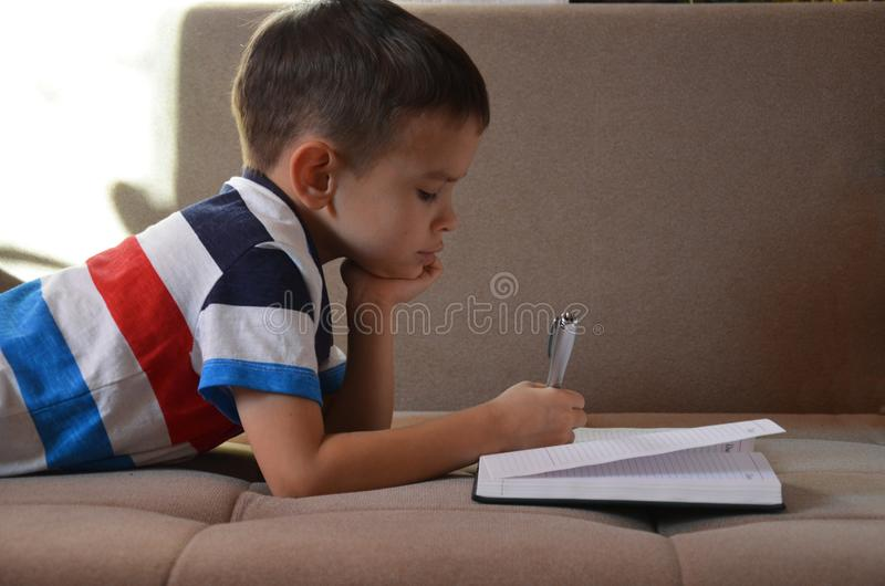 Slut upp pyshandhandstil på papper, ungehandstil på soffan i vardagsrum, studentbarnpojke som rymmer färgblyertspennan som lär ho royaltyfri fotografi