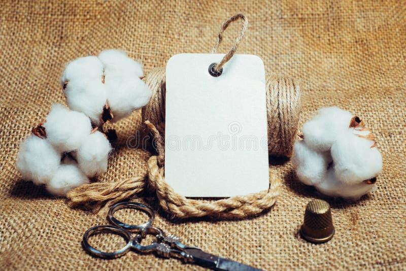 Slut upp rektangelpappersetikett med repfingerborg, sax på tappningtyger bredvid bomullsbollar Falsk övre bomullsmall royaltyfri fotografi