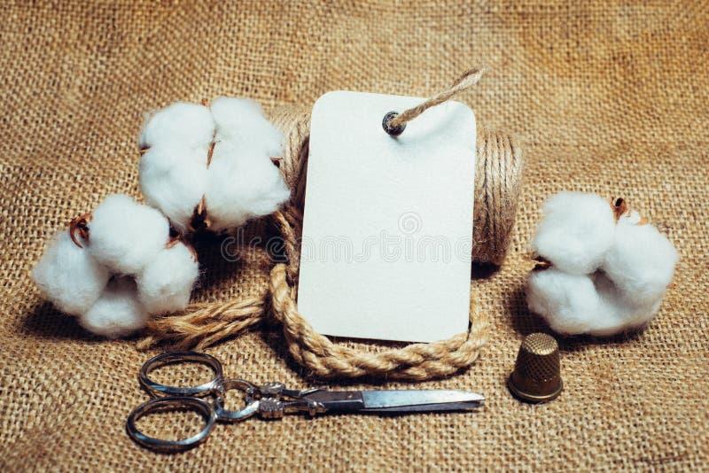 Slut upp rektangelpappersetikett med repfingerborg, sax på tappningtyger bredvid bomullsbollar Falsk övre bomullsmall arkivbilder