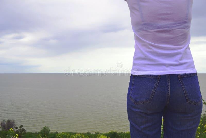 Slut upp sexig kvinnar?v med jeans p? stranden p? suddighetshavbakgrund p? soliga dagar och trevligt v?der i lopp och ferie royaltyfri foto
