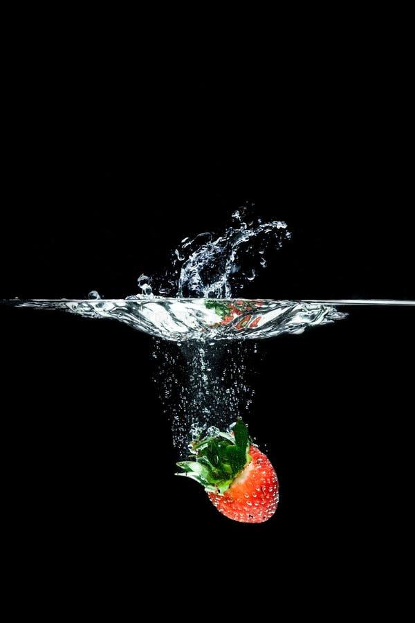 slut upp sikten av jordgubben som faller in i vatten royaltyfri bild