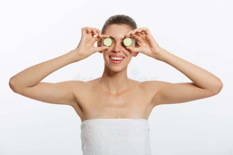 Slut upp skönhetståenden av en lycklig härlig halv naken kvinna med en handduk som slås in runt om hennes hållande gurka för krop royaltyfria foton
