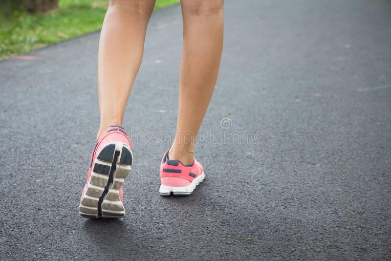 Slut upp skor, ben sikten för sportlöparekvinnan som tillbaka kör, flickan som in går, parkerar Sportövningsfördel royaltyfri foto