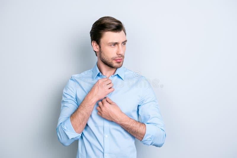 Slut upp ståenden av den attraktiva mannen som korrigerar knappar på hans bl fotografering för bildbyråer