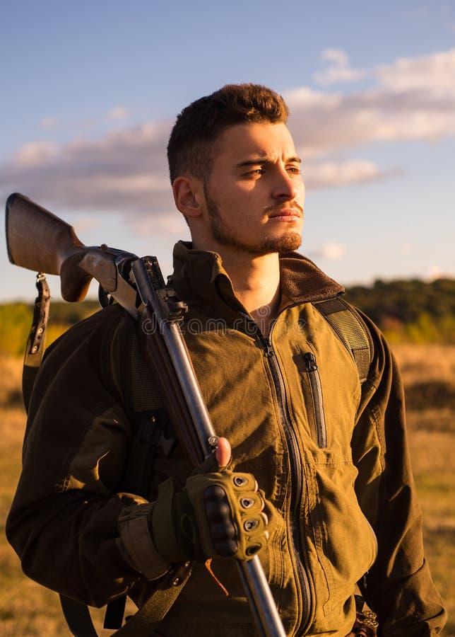 Slut upp ståenden av den hamdsome jägaren Jägare med hagelgevärvapnet på jakt Jägare som siktar geväret i skogjägareman royaltyfri foto