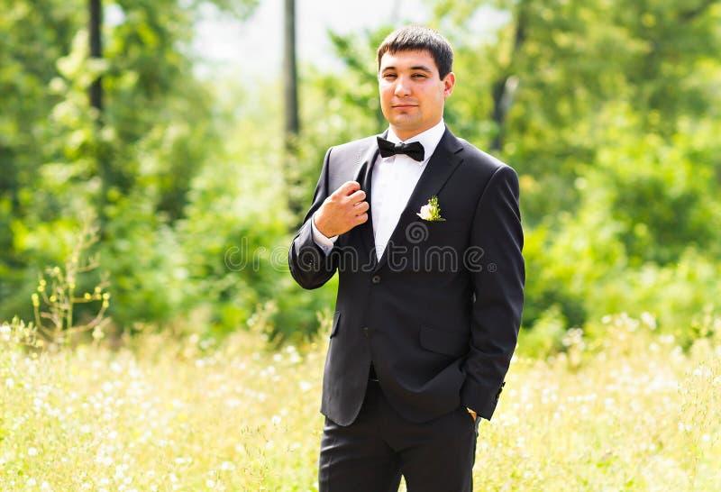 Slut upp ståenden av den stiliga stilfulla brudgummen i svart klassisk dräkt utomhus arkivbild
