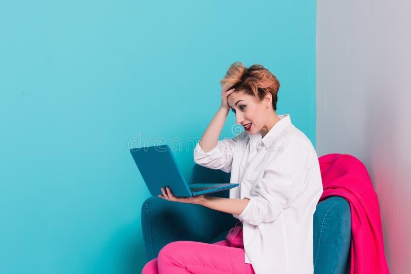Slut upp ståenden av den trötta flickan med missbelåtet framsidauttryck som ser hennes anteckningsbokskärm med kopieringsutrymme  arkivfoto