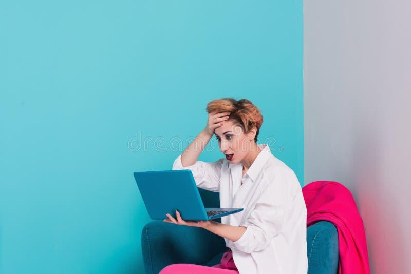 Slut upp ståenden av den trötta flickan med missbelåtet framsidauttryck som ser hennes anteckningsbokskärm med kopieringsutrymme  royaltyfri foto