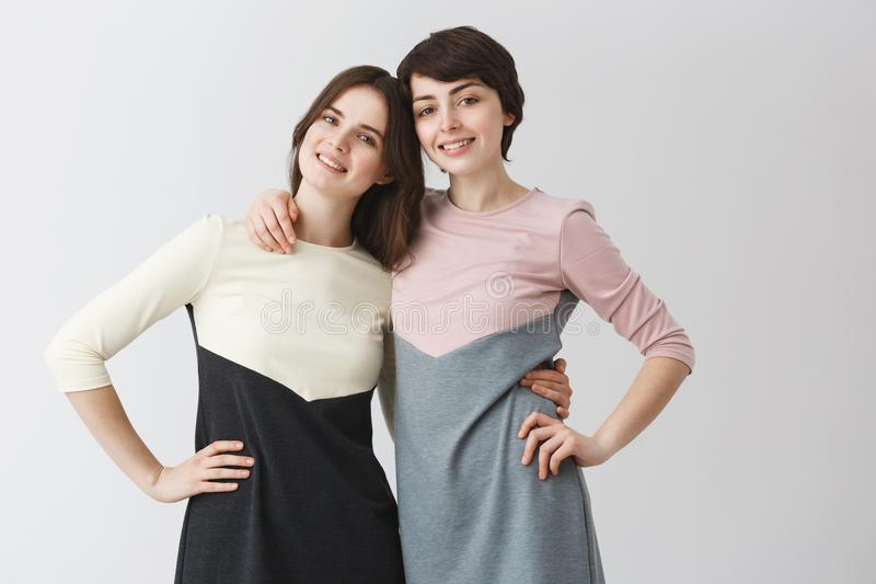 Slut upp ståenden av glade lesbiska par som kramar sig och att rymma handen på midjan som poserar för foto, i att matcha fotografering för bildbyråer