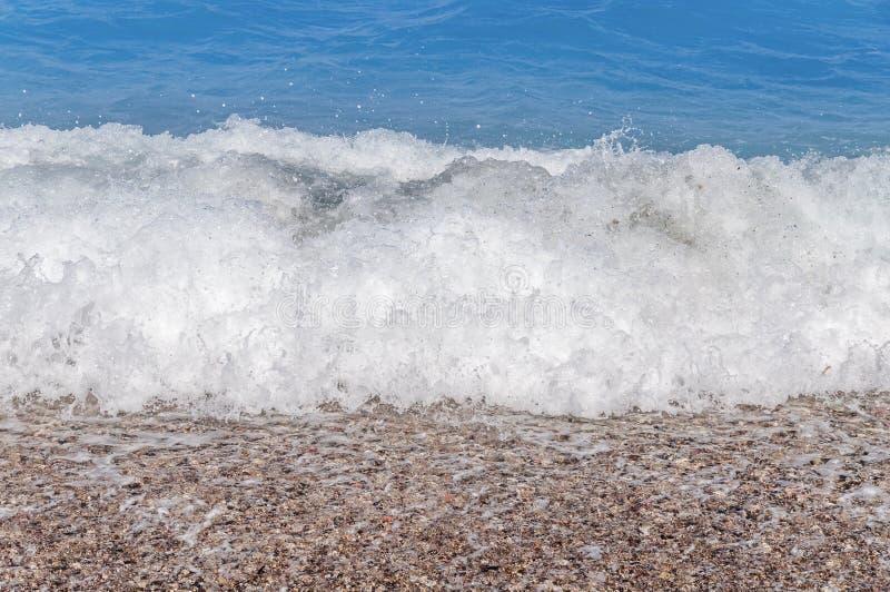 Slut upp stor blå havsvattenvåg på sandstranden med bubblor arkivbilder