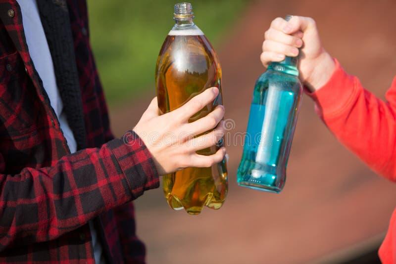 Slut upp tonåringar som tillsammans dricker alkohol royaltyfria foton