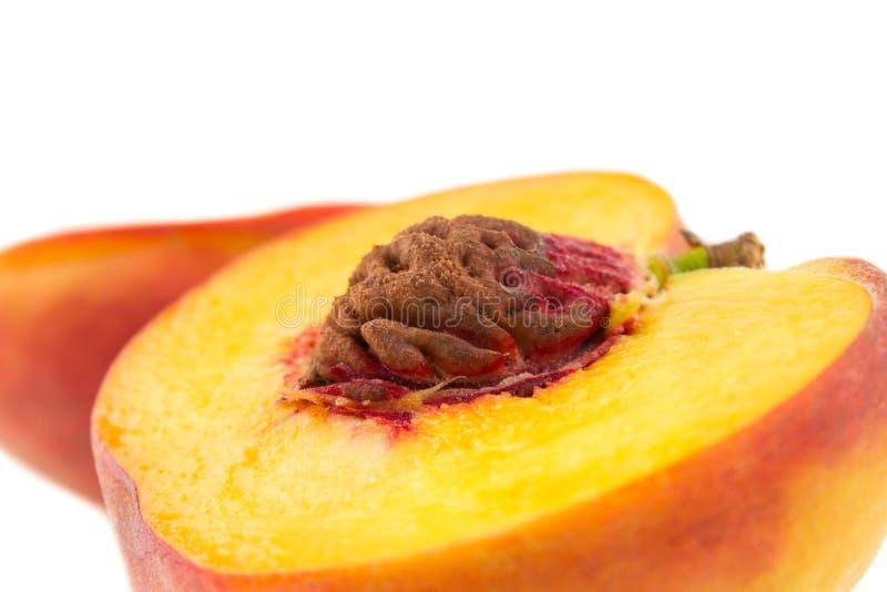 Slut upp två halvor av persikan med den fokuserade gropen som isoleras på vit royaltyfri bild
